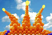 Crown from orange balloons against a blue sky — Stock Photo