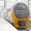 Train in snowstorm departing — Stock Photo