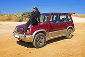 Belle jeune femme assise sur une jeep dans le désert — Photo