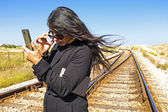 Young beautiful woman rckeading an sms on a railroad track — Stock Photo