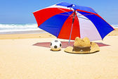 Straw hat, sunglasses and parasol at the beach — Stock Photo