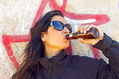 Woman drinking beer in front of a graffiti wall — Stock Photo