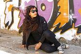 Palenie kobieta w czerni w mur graffiti — Zdjęcie stockowe