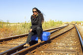 Young woman with her suitcase on a railroad track — Stock Photo