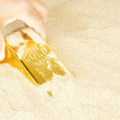 Digging up a goldbar in sand — Stock Photo