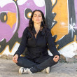 Woman in meditation in front of a graffiti wall — Stock Photo