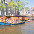 Stock fotografie: AMSTERDAM - APRIL 30: Amsterdam canals full of boats and people