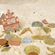House and euro coins disappearing in the sand — Stock Photo