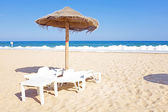 Thatched umbrella and beach chairs on the beach near Lagos Portu — Stock Photo