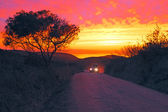 Car driving on a dirt road with an incredible sunset at the west — Stok fotoğraf