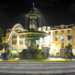 Stock Photo: Night-lit fountain in Rossio Square, Lisbon, Portugal