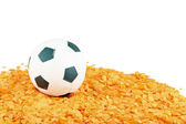 Soccer ball on orange confetti — Stock Photo