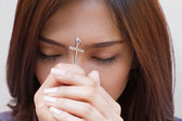 Woman praying with holy cross, closed eye — Stok fotoğraf