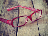Red glasses on wood background retro-vintage style — Stock Photo