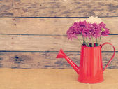 Flowers and watering can old retro vintage style — Stockfoto
