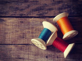 Thread rolls on wood background old retro vintage style — Stockfoto