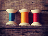 Thread rolls on wood background old retro vintage style — Stock Photo