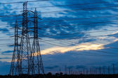 High voltage power transmission lines and pylons — Stock Photo