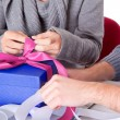Young couple wrapping gift — Stock Photo