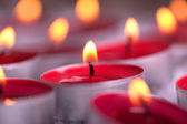 Red lit Tealights with golden flame — Стоковое фото