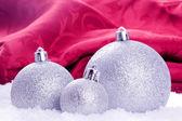 雪と赤の背景でクリスマス ボール — ストック写真