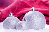 Christmas balls with snow and red background — Stock Photo