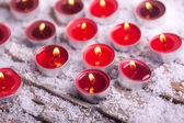 Red lit Tealights with golden flame — Stockfoto