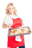 Blond woman with red apron present christmas cookies — Stock Photo
