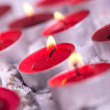 Red lit Tealights with golden flame - Stock Photo