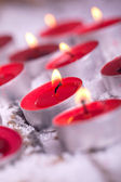 Red lit Tealights with golden flame — Stok fotoğraf