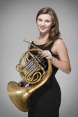 Woman musician with french horn — Stock Photo