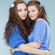 Two young female friends hugging, looking  — Stock Photo