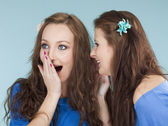 Two young female friends whispering gossip — Stock Photo