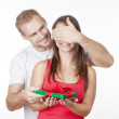 Young man giving a surprise present to his girlfriend — Stock Photo #23698411
