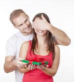 Młody człowiek daje niespodzianka obecny jego dziewczyna — Zdjęcie stockowe