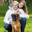 Happy young couple with dog — Stock Photo #33289085