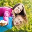 Happy young couple piggybacking, arms outstretched. — Stock Photo