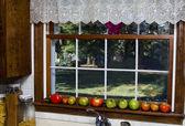 Tomatoes ripening on kitchen window sill — Stock Photo
