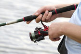 Fisherman holding a spinning closeup — Stock Photo
