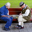 Older play chess on a bench - Stock Photo