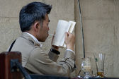 Japanese tourist reads a book in Lvov cafe — Stock Photo