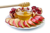Cut into slices of apples, pomegranate and bowl of honey — Stock Photo