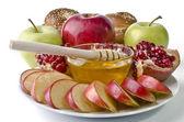 Zátiší - chala, jablka, granátová jablka a mísa medu — Stock fotografie