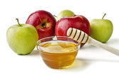 Red and green apples and a bowl of honey — Stock Photo