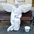 Living statue - a white angel sitting on a bench — Stock Photo