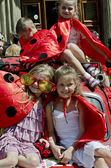 Children dressed as ladybugs sitting on retro car — Stock Photo
