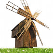 Wooden mill on the green grass isolated over white — Stock Photo