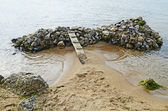 Bridge on a pile of rocks in the sea — Stock Photo