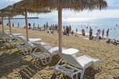 Chaise lounges and beach umbrellas from a reed on a beach — Stock Photo