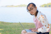 Young girl with laptop on the grass — Stock Photo